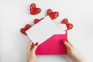 Sobre con una carta en las manos sobre un fondo blanco. foto