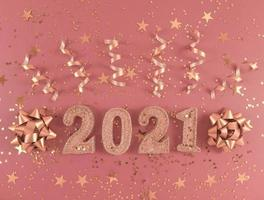 Glittered figures 2021, stars, bows and ribbons on pink background. photo