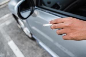 joven fumando en el coche foto