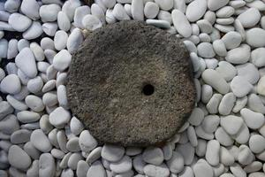 Vintage dark rock surrounded by white rounded stone. photo