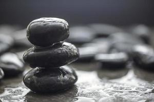 A pile of three Black stones isolated in blurred background. photo
