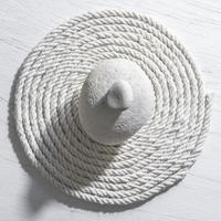 White stone on a central of white rope background photo