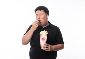 Young funny fat Asian man eating popcorn photo
