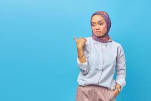 Portrait of beautiful unhappy Asian woman pointing to empty space photo