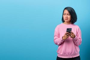 young asian woman holding smartphone unhappy looking sideways photo