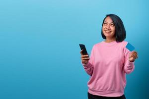 Beautiful asian woman using mobile phone and holding credit card photo