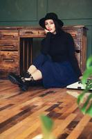Hermosa mujer con sombrero se sienta cerca de la mesa de roble con máquina de escribir vintage foto