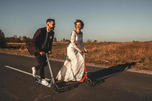 Smiling wedding couple riding a on scooters along the road at sunset photo