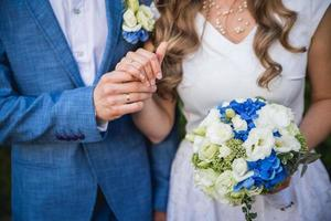 Wedding couple holding hands with a bouquet of flowers and rings photo