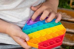 el niño juega con el dedo presionando el colorido pop se inquieta juguete. foto