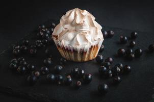 muffin sobre un fondo negro con grosellas. foto
