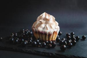 muffin sobre un fondo negro con grosellas. sobre un fondo oscuro foto
