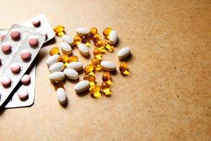 Blister with pink tablets and vitamin D and capsules with fish oil lie chaotically against the background of a sand countertop photo