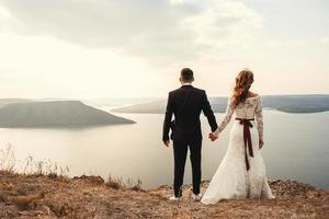Married couple embracing on a mountain photo