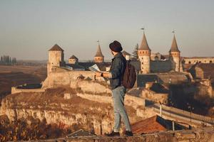 Man in front of an old castle with a map photo