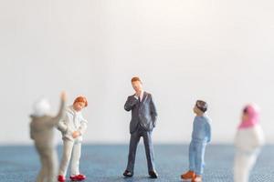 Estudiantes de personas en miniatura de pie con el profesor en el aula. foto