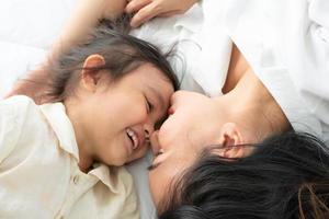 madre e hija acostadas en una cama foto