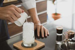 Barista pouring iced coffee photo
