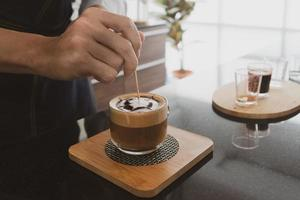 Barista making latte art in cafe photo