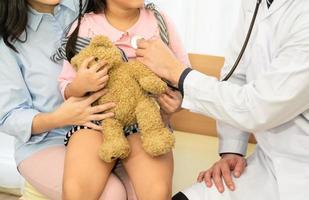 Pediatra examina a un niño pequeño en la clínica del hospital foto