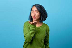 Attractive Asian woman send air kiss on blue background photo