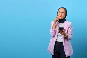 Hermosa mujer asiática piensa en algo y sostiene el teléfono móvil foto