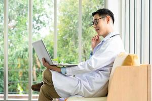Doctor using computer to give consult to patient photo