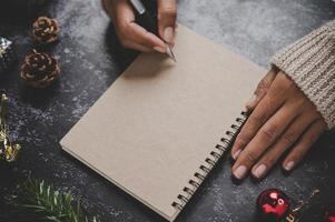 A hand holding a pen to write on a notebook with glasses photo