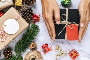 una mano sosteniendo una caja de regalo negra sobre un piso de cemento blanco foto