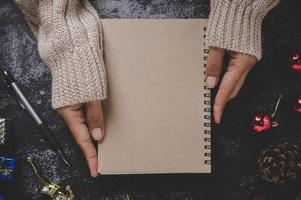 Hand holding a notebook with pen and small gifts photo