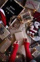 Female hands wrapping christmas gifts in craft paper top view flat lay photo