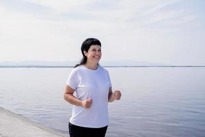 Active laughing senior woman jogging near the riverside photo