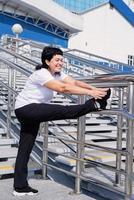 Smiling senior woman doing stretching outdoors on urban background photo