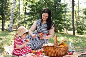 Familia interracial de madre e hija en el parque haciendo un picnic foto