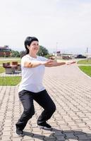 Smiling senior woman squatting outdoors in the park photo