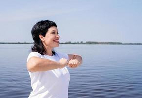 Active and happy senior woman exercising near the riverside photo