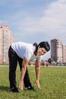 Smiling senior woman warming up stretching outdoors in the park photo