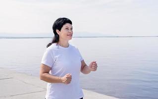 Active senior woman jogging near the riverside photo