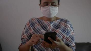 Woman wears face mask scrolling smartphone with data tracking online video