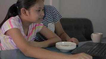 Mother helping and teaching daughter study at home with lesson online video