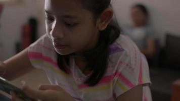 niña jugando juegos en el teléfono inteligente y sentada lejos de la madre en casa video