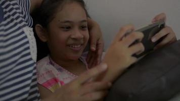 flicka som spelar spel på smartphone med sin mamma i vardagsrummet video