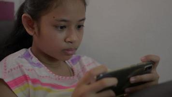 niña disfruta jugando juegos en línea en el teléfono inteligente durante el aislamiento en el hogar video