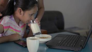 Mom give a glass of fresh milk to daughter while study lesson online video