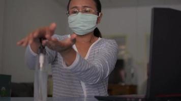 Woman wears face mask sanitizing hands on working desk video