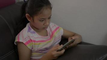 niña disfruta jugando juegos en el teléfono inteligente y sentada en la sala de estar video