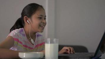 Girl talking with distance teacher during online lesson at home video