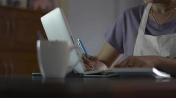 mulher trabalhando em tablet digital e calculando despesas em casa video