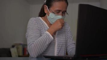 Woman wears face mask coughing during working on the desk at home video