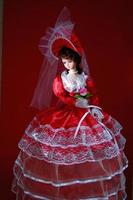 A charming and graceful doll with bright red bridal dress photo